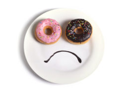 40416419 - smiley sad face worried about overweight made on dish with donuts as eyes and chocolate syrup as mouth in sugar and sweet addiction , diet and nutrition concept isolated on white background